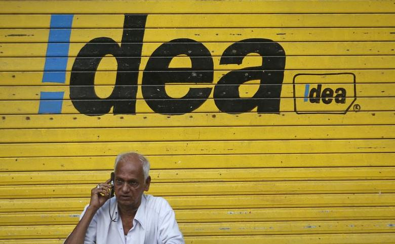 A man speaks on his mobile phone as he sits in front of a shop displaying the Idea Cellular Ltd's logo on its shutter in Mumbai April 28, 2014. REUTERS/Danish Siddiqui