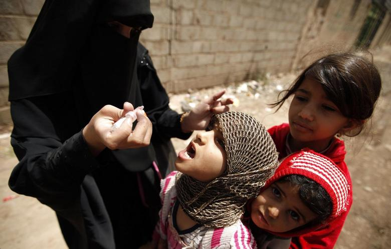 A health worker administers drops of polio vaccine to children in an outskirt of the Yemeni capital Sanaa April 7, 2014.  REUTERS/Khaled Abdullah