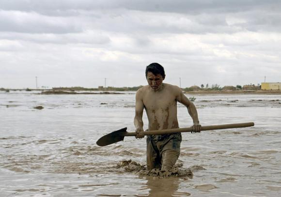 An Afghan man searches for his belongings after a flood at Jawzjan province, April 25, 2014. REUTERS/Stringer