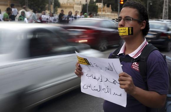 A demonstrator looks on with a sign reading ''I am against the military courts for civilians'' taped over his mouth during a human chain by members of the April 6 movement and liberal activists against a law restricting demonstrations as well as the crackdown on activists and calling for the release of activists in detention in front of El-Thadiya Egyptian Presidential in Cairo, April 23, 2014. The sign reads ''Freedom for Abdallah Elshamy, an Egyptian journalist for Al Jazeera Arabic broadcast.'' REUTERS/Amr Abdallah Dalsh