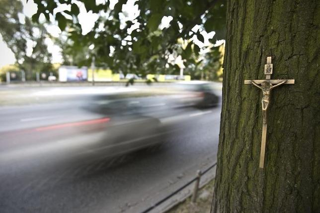 A cross placed by the side of the road in the centre of Warsaw August 8, 2009 marks the spot where a person was killed in a traffic accident. Between July 17, 2009 and July 19, 2009, 50 people have died and 703 injured in 458 car accidents, according to Karol Jakubowski of the Police press department. REUTERS/Peter Andrews
