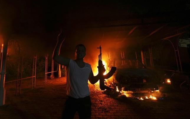 A protester reacts as the U.S. Consulate in Benghazi is seen in flames during a protest by an armed group said to have been protesting a film being produced in the United States September 11, 2012. REUTERS/Esam Al-Fetori