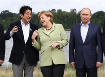 Премьер Японии Синдзо Абэ (слева), канцлер Германии Ангела Меркель (в центре) и президет РФ Владимир Путин на саммите G8 под Эннискилленом 18 июня 2013 года.  Канцлер Германии Ангела Меркель и японский премьер Синдзо Абэ заверили в среду, что ведущие индустриальные державы сохранят единство в отношении санкций против России, если потребуется новый раунд, несмотря на угрозы Москвы отомстить иностранным энергокомпаниям.  REUTERS/Yves Herman