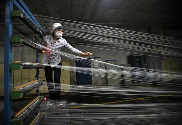 An employee works at a textile factory in Wuhan, Hubei province, April 30, 2014. REUTERS/Stringer/Files