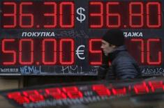 Мужчина проходит мимо пункта обмена валют в Москве 3 марта 2014 года. Рубль стабилен на торгах понедельника в условиях низкой межпраздничной рыночной ликвидности, свою роль в плавном течении торгов может играть и нерабочий день в Англии; несмотря на затишье, ситуация вокруг Украины останется одним из важных факторов курсообразования рубля в ближайшее время. REUTERS/Maxim Shemetov
