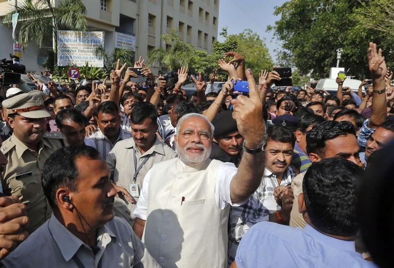 Hindu nationalist Narendra Modi (C), the prime ministerial candidate for the main opposition Bharatiya Janata Party (BJP), shows his ink-marked finger to his supporters after casting his vote at a polling station during the seventh phase of general election in Ahmedabad April 30, 2014. REUTERS/Amit Dave