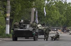 Пророссийские вооруженные сепаратисты едут на БТР около Славянска на востоке Украины, 5 мая 2014 год. Столкновение украинских войск и пророссийских сепаратистов около Славянска с применением бронетехники унесло полтора десятка жизней и стало одним из самых кровавых боев за время противостояния Киева с ополченцами, несколько недель удерживающими контроль над городом. REUTERS/Baz Ratner