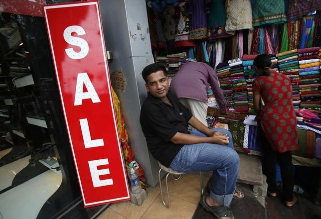 A salesman waits for customers outside a clothing store at a shopping arcade in Mumbai July 3, 2013. REUTERS/Vivek Prakash/Files