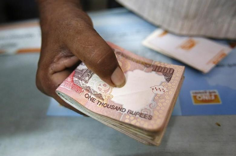 A customer hands a bundle of rupee notes to a teller at a financial institution in Mumbai July 2, 2013. REUTERS/Vivek Prakash/Files