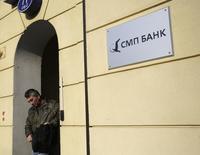 Вывеска с логотипом СПМ-банка у центрального офиса банка в Москве 24 марта 2014 года. Входящий в топ-50 банков РФ СМП-банк, попавший под санкции США, возобновил работу с валютными вкладами, сообщил банк. REUTERS/Maxim Zmeyev