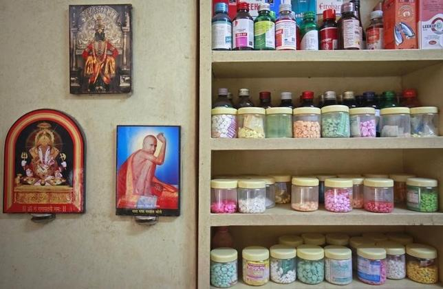 Pictures of Hindu gods hang beside a medicines rack inside a clinic in Pune August 27, 2012. Danish Siddiqui/Files