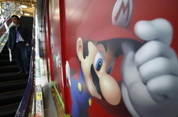 A shopper rides the escalator past Nintendo advertisements at an electronics retail store in Tokyo January 20, 2014.  REUTERS/Yuya Shino/Files