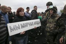 Женщина держит плакат перед украинскими военными у блокпоста близ Славянска 2 мая 2014 года. По утрам 28-летняя шпаклевщица Александра оставляет дома свою дочь, засовывает за пояс сигнальный пистолет и идет к баррикадам в центр родного города Славянска. REUTERS/Baz Ratner