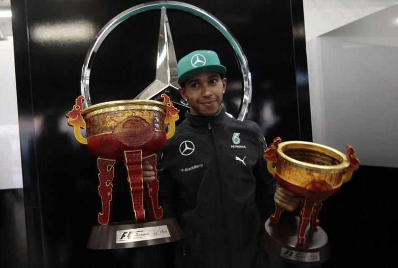First-placed Mercedes Formula One driver Lewis Hamilton of Britain poses with his trophies during a photo call after the Chinese F1 Grand Prix at the Shanghai International Circuit April 20, 2014. REUTERS/Aly Song