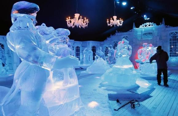 A sculptor works near sculptures based on characters from Disney movies at the Snow and Ice Sculpture Festival in Bruges November 20, 2013. REUTERS/Francois Lenoir/Files