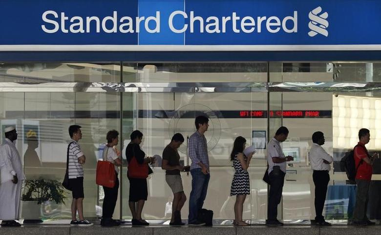 People queue up outside a Standard Chartered Bank branch before operation hours at the central business district in Singapore January 23, 2014. REUTERS/Edgar Su/Files