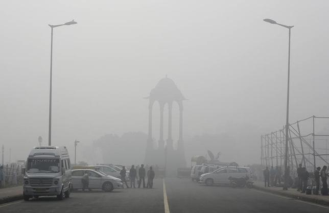 Vendors selling drinks stand beside vehicles near the India Gate war memorial on a smoggy day in New Delhi February 1, 2013.  REUTERS/Adnan Abidi