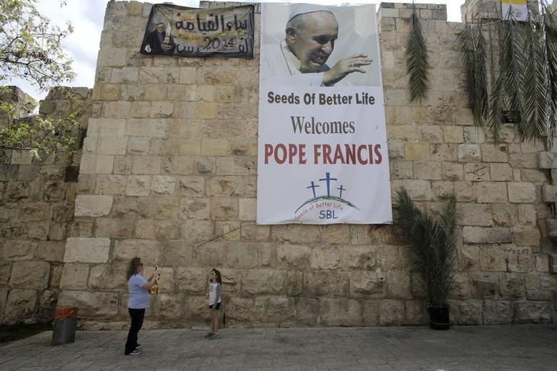 A woman takes a photo of a girl with a mobile phone in front of a banner depicting Pope Francis outside Jerusalem's Old City April 13, 2014.  REUTERS/Ammar Awad