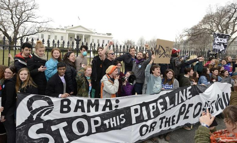 Environmentalists, many of whom have zip-tied themselves to the fence of the White House in Washington, rally and call on U.S. President Barack Obama to reject the Keystone XL pipeline in this March 2, 2014 file photo. REUTERS/Mike Theiler/Files