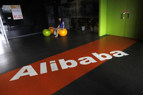 An employee sits next to a logo of Alibaba during a media tour organised by government officials at the company's headquarters on the outskirts of Hangzhou, Zhejiang province, June 20, 2012.  REUTERS/Carlos Barria/Files