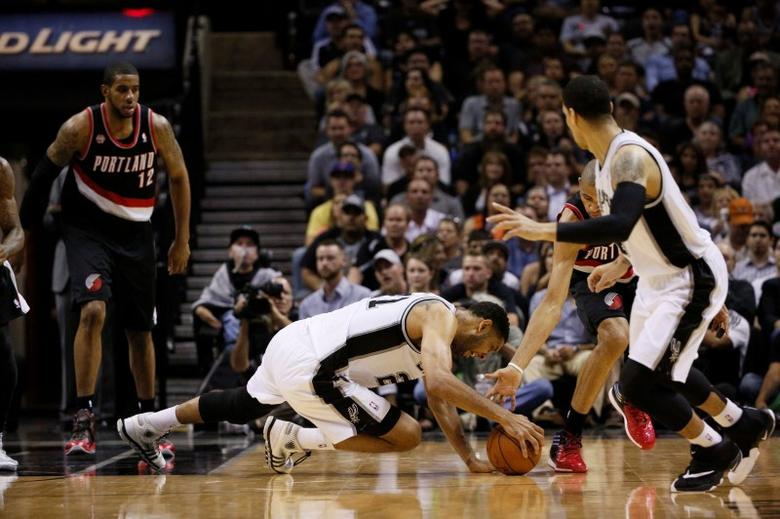 May 8, 2014; San Antonio, TX, USA; San Antonio Spurs forward Tim Duncan (left) and Portland Trail Blazers forward Nicolas Batum (right) dive for a loose ball in game two of the second round of the 2014 NBA Playoffs at AT&T Center. Soobum Im-USA TODAY Sports