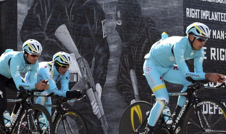The Astana cycling team pass a loyalist paramilitary mural painted on a wall in east Belfast as they make their way around the route of the Giro d'Italia team time trial May 9, 2014. REUTERS/Cathal McNaughton