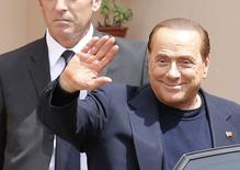 Former Italian Prime Minister Silvio Berlusconi waves as he leaves the Sacred Family Foundation in Cesano Boscone, a small town on the outskirts of Milan May 9, 2014. REUTERS/Stefano Rellandini
