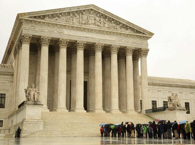 People line up in the rain outside of the U.S. Supreme Court in Washington April 29, 2014. REUTERS/Gary Cameron