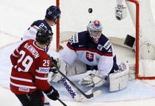 Slovakia's goaltender Jan Laco (R) fails to save a goal of Canada's Nathan MacKinnon (L) during the third period of their men's ice hockey World Championship group A game at Chizhovka Arena in Minsk May 10, 2014. REUTERS/Vasily Fedosenko
