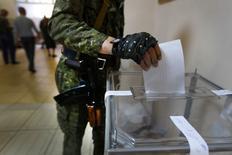 Вооруженный пророссийский ополченец опускает бюллетень в урну на избирательном участке в Славянске 11 мая 2014 года. Сепаратисты объявили об уверенной победе на референдумах о самоуправлении восточных областей Украины, которая для одних означает независимость, а для других - союз с Россией. Кремль заявил, что относится к результатам голосования с уважением и рассчитывает на реализацию его итогов цивилизованным путем, Киев же назвал плебисцит фарсом. REUTERS/Yannis Behrakis