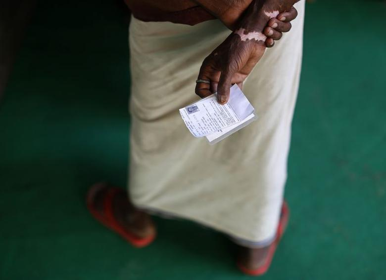 A voter holds his vote paper as he waits to cast his vote at a polling station in the final phase of the general election in Varanasi in Uttar Pradesh May 12, 2014.  REUTERS/Ahmad Masood
