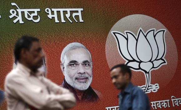 Men walk past a hoarding of Hindu nationalist Narendra Modi, the prime ministerial candidate for Bharatiya Janata Party (BJP), outside the party headquarters in New Delhi May 12, 2014. The hoarding reads, ''Excellent India''. REUTERS/Adnan Abidi