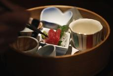 "A chef places wasabi next to slices of tuna sashimi as he makes a ""Gakuyameshi"" lunch box at a Japanese-style restaurant in Tokyo in this December 5, 2013 file photograph.   REUTERS/Toru Hanai/Files"