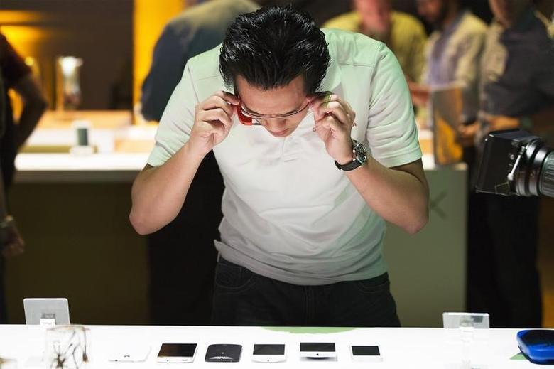 A man uses Google Glass to photograph examples of Motorola's new Moto X phone next to other mobile phones at a launch event in New York, August 1, 2013. REUTERS/Lucas Jackson/Files
