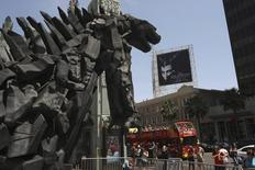 A tourist bus passes a statue of movie monster Godzilla in front of the TCL Chinese Theatre IMAX forecourt on Hollywood Boulevard in the Hollywood section of Los Angeles, California, May 9, 2014. REUTERS/David McNew