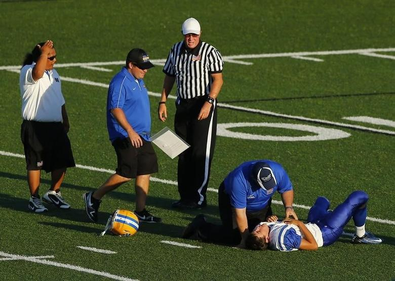 A Mira Mesa junior varsity high school football player is attended to by training staff after being hit by an Oceanside Pirates player during their game in Oceanside, California September 14, 2012. REUTERS/Mike Blake