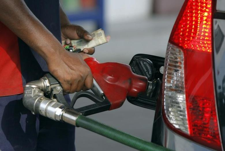 An employee fills a vehicle with petrol at a fuel station in New Delhi June 25, 2010. REUTERS/Mukesh Gupta/Files