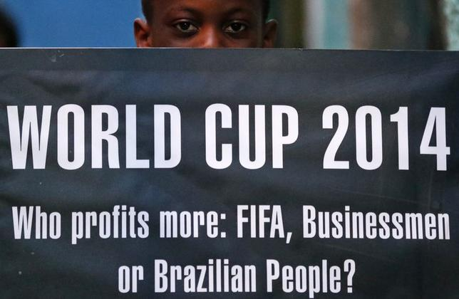 A boy holds up a banner as children sit at what is meant to represent a public school classroom, during a protest against the 2014 World Cup, organised by non-governmental organisation (NGO) Rio de Paz (Rio of Peace) at the Jacarezinho slum in Rio de Janeiro May 14, 2014.  REUTERS/Sergio Moraes