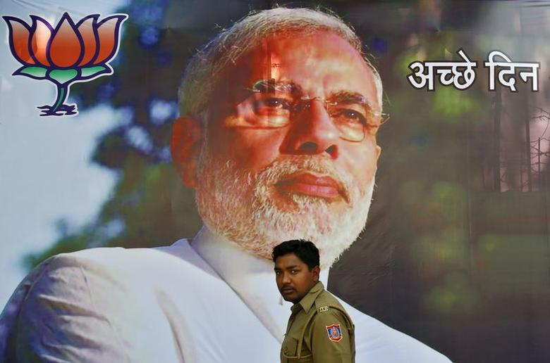 A policeman stands in front of a boarding with an image of Narendra Modi, the prime ministerial candidate for Bharatiya Janata Party (BJP), in New Delhi May 16, 2014. REUTERS/Anindito Mukherjee