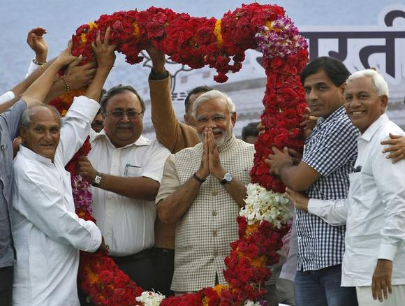 Hindu nationalist Narendra Modi, the prime ministerial candidate for India's main opposition Bharatiya Janata Party (BJP), gestures as he receives a garland from his supporters during a public meeting in Vadodara, in Gujarat, May 16, 2014. REUTERS/Amit Dave