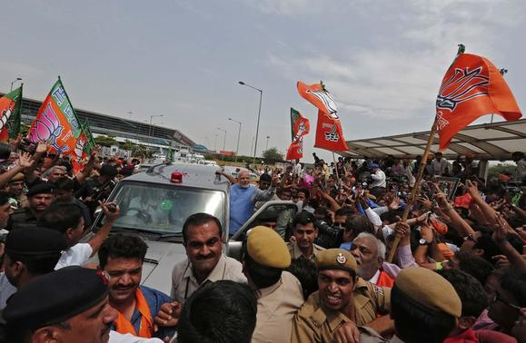 Hindu nationalist Narendra Modi, the prime ministerial candidate for India's Bharatiya Janata Party (BJP), gestures towards his supporters from his car during a road show upon his arrival at the airport in New Delhi May 17, 2014. REUTERS/Adnan Abidi