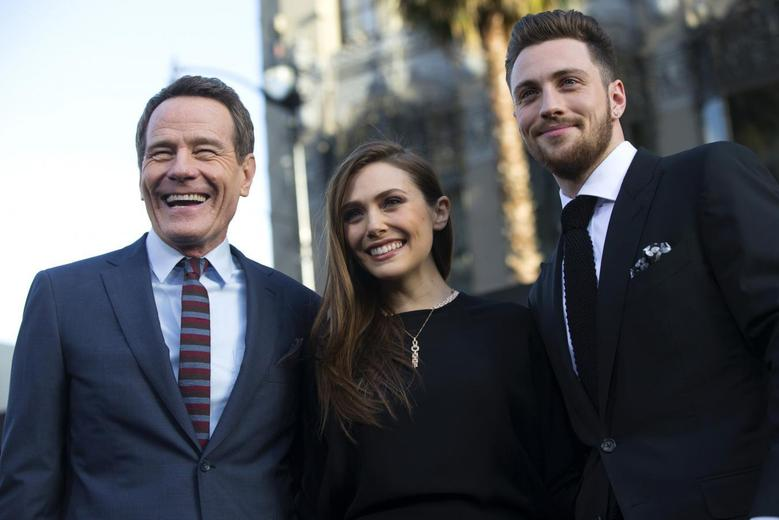 Cast members Bryan Cranston (L), Elizabeth Olsen (C) and Aaron Taylor-Johnson pose at the premiere of ''Godzilla'' at the Dolby theatre in Hollywood, California May 8, 2014.  REUTERS/Mario Anzuoni
