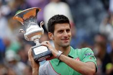 Novak Djokovic of Serbia holds the trophy after winning the men's singles final match against Rafael Nadal of Spain at the Rome Masters tennis tournament May 18, 2014. REUTERS/Giampiero Sposito