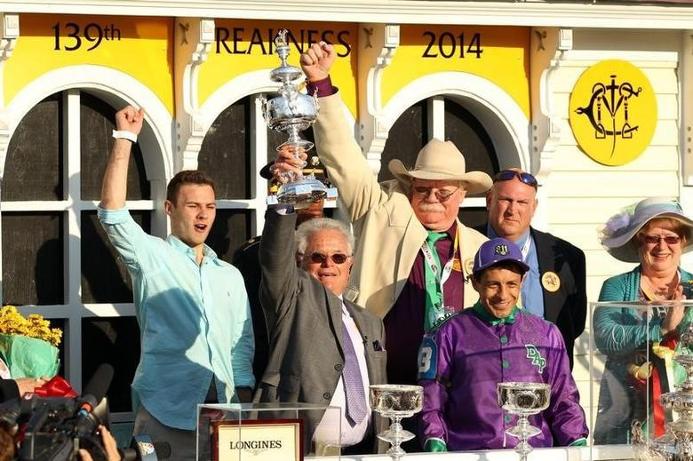 May 17, 2014; Baltimore, MD, USA; California Chrome trainer Art Sherman (holding trophy), jockey Victor Espinoza and owner Steven Coburn celebrate after winning the 139th Preakness Stakes at Pimlico Race Course. Mitch Stringer-USA TODAY Sports