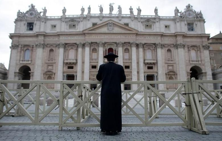 A priest stands in front of Saint Peter's Basilica as a red curtain has been put on the central balcony, called the Loggia of the Blessings, at the Vatican March 11, 2013.  REUTERS/Christian Hartmann