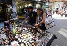 People look at marijuana smoking paraphernalia in a street market in downtown Montevideo March 10, 2014.  REUTERS/Andres Stapff