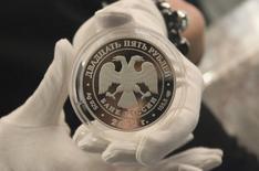 Коллекционная монета номиналом 25 рублей на презентации в Москве 25 апреля 2012 года. Рубль открыл торги минимальным ростом к доллару и бивалютной корзине после того, как накануне продемонстрировал мини-ралли, подстегиваемый экспортными продажами и наверстывая отставание от мировых валют благодаря снижению политических рисков. REUTERS/Yana Soboleva