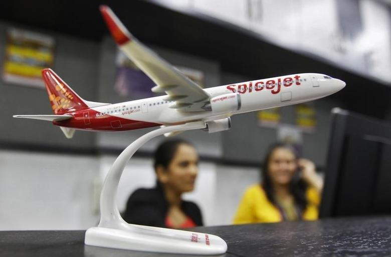 Employees work inside a travel agency office besides a model of a SpiceJet aircraft in Ahmedabad February 14, 2014. REUTERS/Amit Dave/Files