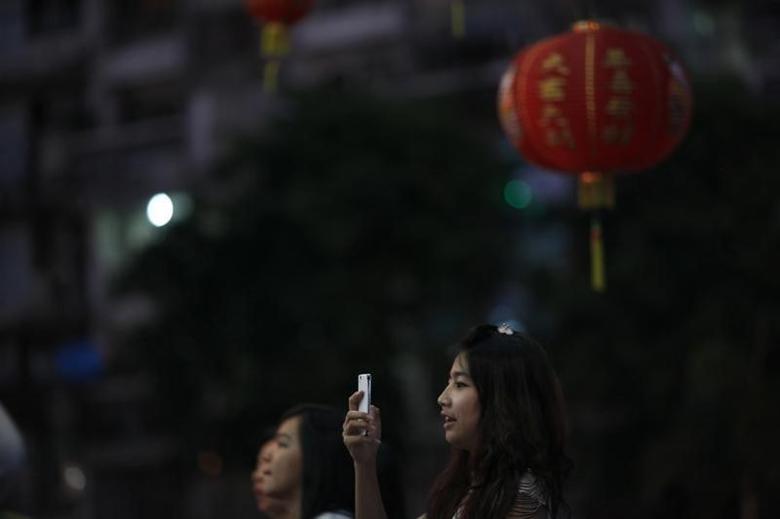 A girl uses her phone at Chinatown in Yangon February 9, 2013. REUTERS/Soe Zeya Tun