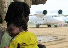 A south Sudanese woman carries her child as she looks at a humanitarian aid cargo plane in Akuem village in southern Sudan September 15, 2005.  REUTERS/David Mwangi